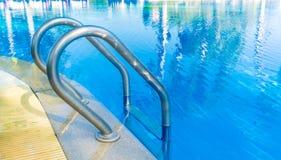 Échelle de barre de piscine dans l'eau bleu-clair Photographie stock libre de droits