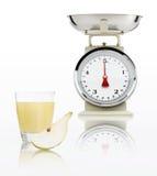 Échelle de nourriture avec le verre de jus de poire d'isolement sur le fond blanc Photo stock