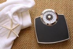 Échelle de poids avec l'essuie-main sur le tapis Image libre de droits