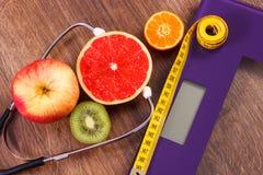 Échelle de salle de bains électronique, centimètre et fruits frais avec le stéthoscope, le régime et les modes de vie sains Photographie stock libre de droits