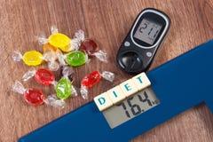Échelle de salle de bains et glucometer électroniques avec le résultat de la mesure et des sucreries colorées, diabète, amincissa Image stock