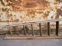 Échelle devant un récipient rouillé Photos libres de droits