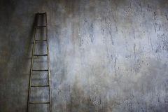 Échelle en bois se penchant contre le mur texturisé Le concept de l'échelle de carrière photographie stock