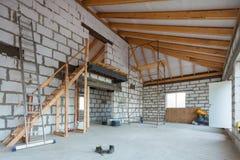 Échelle, pièces d'échafaudage et matériau de construction sur le plancher pendant sur la retouche, rénovation, extension photographie stock