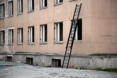 Échelle près du bâtiment avec les fenêtres cassées Image stock