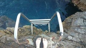 Échelle vers la mer avec le pied Image stock