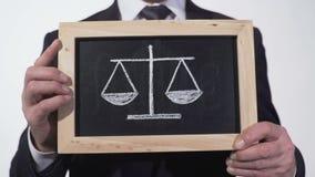 Échelles de justice dessinées sur le tableau noir dans des mains d'avocat, le pour de décision - et - le contre banque de vidéos