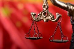 Échelles de justice, Justitia, Madame Justice devant le drapeau de la Chine Image stock