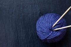 Écheveau de fil pourpre avec les aiguilles de tricotage en bambou avec le fond noir d'ardoise Photos stock