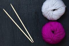 Écheveau de fil rose et gris avec les aiguilles de tricotage en bambou avec le fond noir d'ardoise Image libre de droits