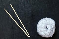 Écheveau du fil blanc avec les aiguilles de tricotage en bambou Photo stock