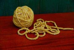 Écheveau jaune de fil de laine sur la table rouge Photo stock