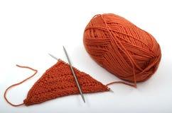 Écheveau orange de laine et de needls de tricotage Photos stock