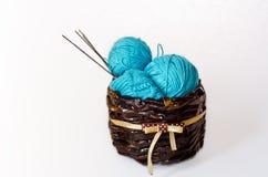 Écheveaux de fil bleu et du tricotage de ces amorçages dans un bac. Photographie stock