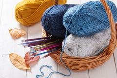Écheveaux des aiguilles de fil et de tricotage dans le panier Image libre de droits