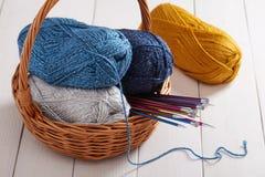 Écheveaux des aiguilles de fil et de tricotage dans le panier Photos libres de droits