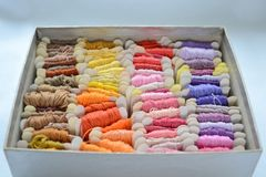 Écheveaux des fils colorés dans couleurs chaudes pour la broderie et couture dans la boîte photographie stock