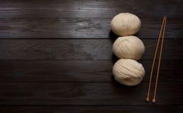 Écheveaux et aiguilles de tricotage en bois sur une table en bois brune Photos stock
