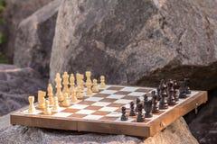 Échiquier avec des pièces d'échecs sur la pierre avec la roche sur le backgrou Photo libre de droits