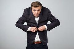 Échouer dans le concept d'affaires Jeune homme désordonné dans le grand costume essayant d'attacher un bouton Il se sent nerveux image stock