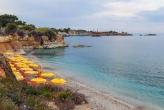 Échouez avec de l'eau le sable blanc et bleu d'espace libre dans la belle baie avec des lits du soleil et des parapluies, Crète,  Photographie stock