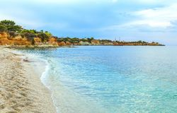 Échouez avec de l'eau le sable blanc et bleu d'espace libre dans la belle baie avec des lits du soleil et des parapluies, Crète,  Photos stock