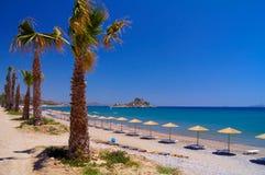 Échouez avec des parasols et des paumes sur l'île de Kos en Grèce photographie stock libre de droits