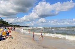 Échouez avec des vagues et des nuages sur un ciel bleu images stock