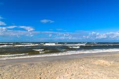 Échouez avec des vagues et des nuages sur un ciel bleu photos stock