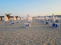 Échouez dans le lever de soleil avec des chaises et des parapluies de plage images libres de droits