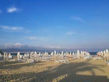 Échouez dans le lever de soleil avec des chaises et des parapluies de plage Photo stock