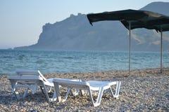 Échouez, des chaises de plate-forme, mer, montagnes, canapé du soleil, cailloux Photo libre de droits