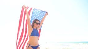 Échouez la femme de bikini avec la marche insouciante de drapeau des USA le long de l'eau sur la plage Concept du Jour de la Décl banque de vidéos