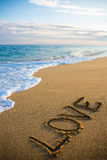 Échouez le fond avec amour de mot écrit en sable Photographie stock