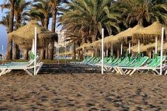 Échouez le parapluie de chaise longue et de plage à la plage sablonneuse isolée Costa del Sol (côte du Sun), Malaga en Andalousie Image libre de droits