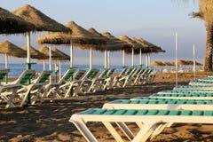 Échouez le parapluie de chaise longue et de plage à la plage sablonneuse isolée Costa del Sol (côte du Sun), Malaga en Andalousie Photographie stock
