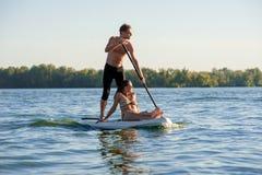 Échouez les couples d'amusement tiennent dessus le panneau de palette SUP02 Images stock