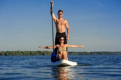 Échouez les couples d'amusement tiennent dessus le panneau de palette SUP04 Photographie stock libre de droits