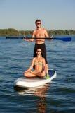 Échouez les couples d'amusement tiennent dessus le panneau de palette SUP03 Photo libre de droits