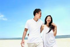 Échouez les couples dans la robe blanche ayant l'amusement riant ensemble Image libre de droits