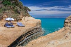 Échouez les lits pliants et le parapluie sur une falaise au-dessus de la mer bleue Images stock