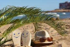 Échouez les pantoufles avec les visages heureux peints et un chapeau avec des lunettes de soleil sous des palmettes sur le sable  Images libres de droits