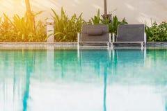 Échouez les sièges près de la piscine avec la lumière du soleil douce Photo libre de droits