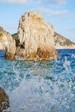 Éclabousse d'une vague et d'une grande roche qui émerge de la mer Images libres de droits