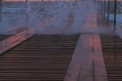 Éclabousse des vagues par le pilier en bois du beau paysage marin des vagues roses de coucher du soleil, de pilier et de tempête  photographie stock