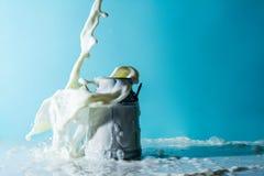 Éclabousse du lait, jet de courant de lait verse le versement dans une boîte de lait sur un fond bleu Images libres de droits