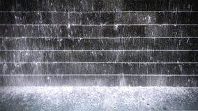 Éclaboussement de l'eau au-dessus du mur carrelé cascadé et de l'étang image stock