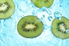 Éclaboussement de l'eau sur des tranches de kiwi sur le fond bleu Photographie stock libre de droits