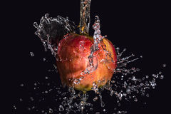 Éclaboussement de l'eau sur la pomme Photo stock