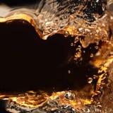 Éclaboussement de la boisson alcoolisée sur un fond noir Photographie stock